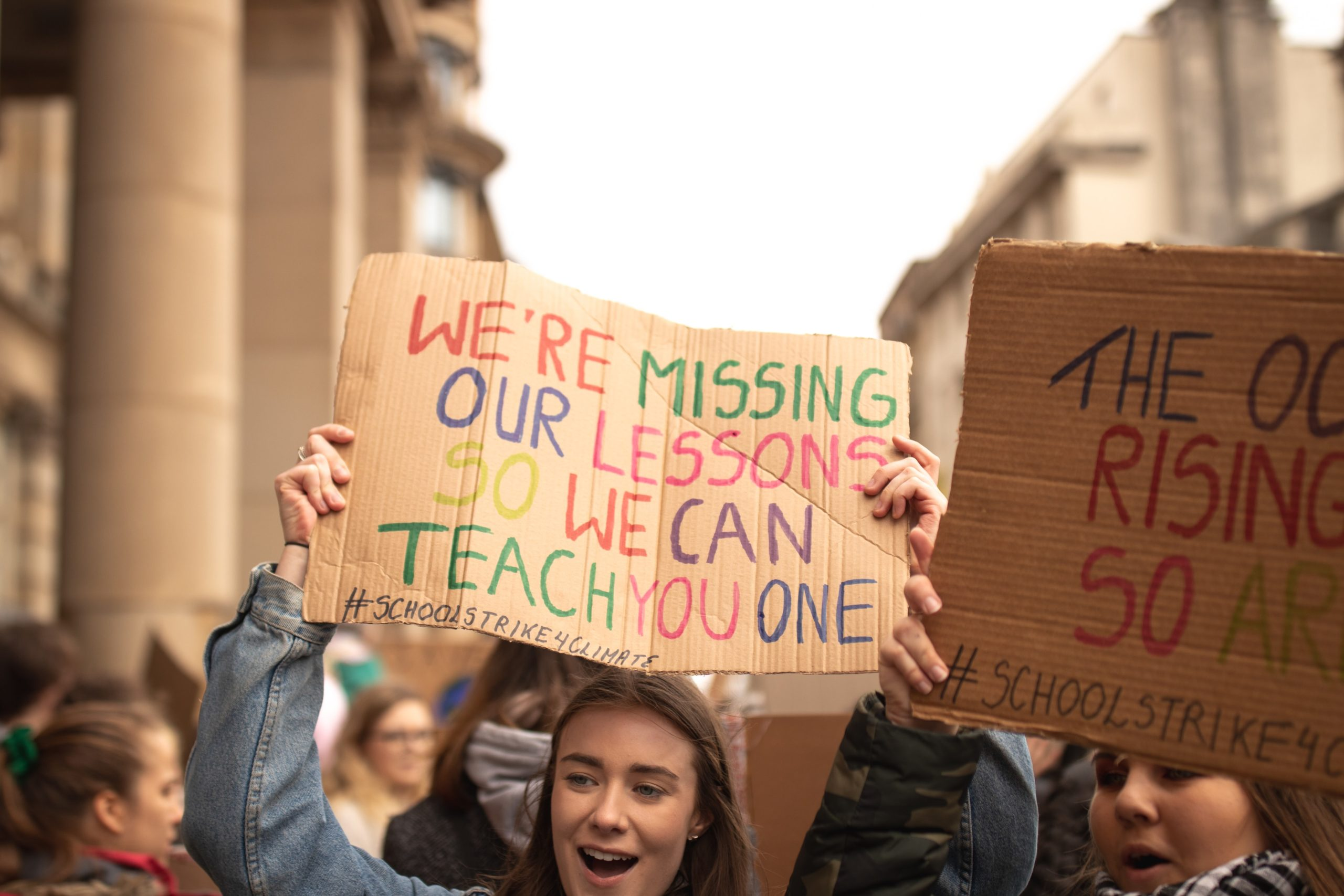Young person at a climate change strike holdingup a sign that reads